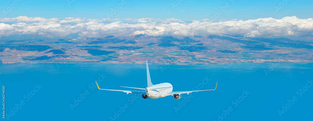 Fototapeta White airplane taking off from the airport - White commercial airplane flying over city