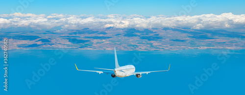 Fototapeta White airplane taking off from the airport - White commercial airplane flying over city obraz