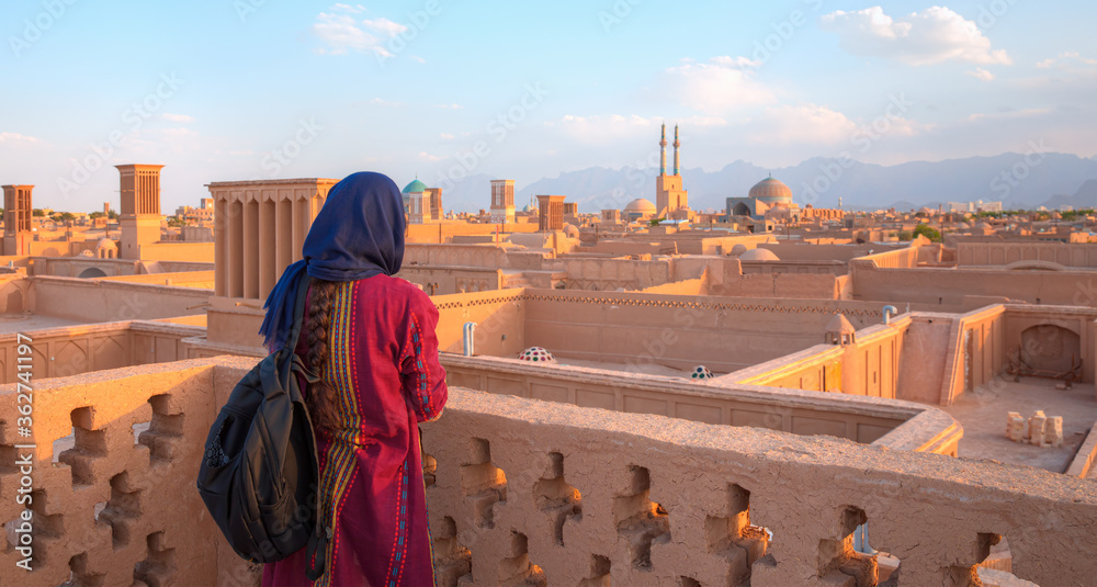 Fototapeta Iranian girl in traditional clothes take a photo - Historic City of Yazd with famous wind towers - Yazd, Iran