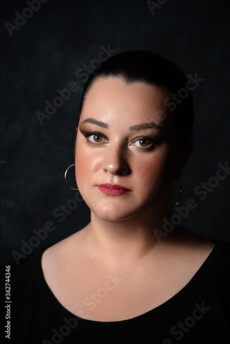Photo portrait of a plump beautiful girl with a serious face on a dark background