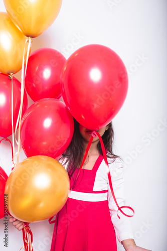 Fototapeta Girl With Red And Orange Balloons Standing Against White Background