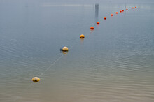 Line Of Yellow And Orange Buoys Strung Successively On Rope Stretched On Greenish Azure Surface Of Water, Covered With Small Ripples Along The Coastal Zone Fencing The Shallow Water Of The Lake