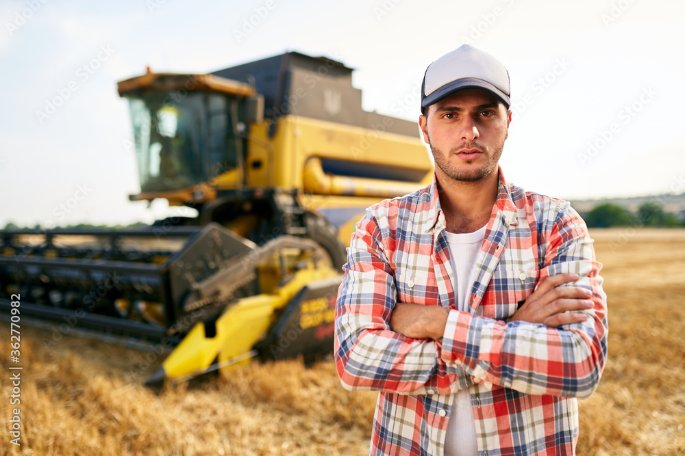 Fototapeta Portrait of proud harvester machine driver with hands crossed on chest. Farmer standing at his combine. Agronomist looking at camera. Rancher at harvesting work on stubble of harvested wheat field.