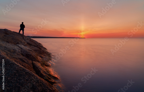 sunset on the shore of Lake Ladoga and the silhouette of a man Canvas Print