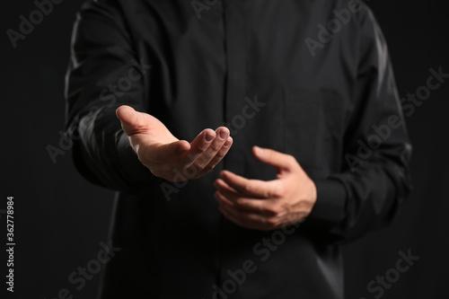 Fototapeta Handsome young priest on dark background, closeup obraz