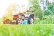 Leinwanddruck Bild - Mowing lawns. Lawn mower on green grass. Mower grass equipment. Mowing gardener care work tool close up view. Sunny day.