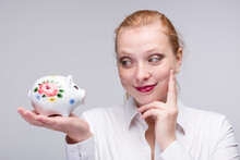 Young Red Haired Woman Looks At Her Little Piggy Bank