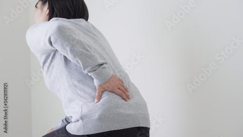 腰痛の女性 Fotobehang