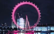 Illuminated Ferris Wheel By River At Night
