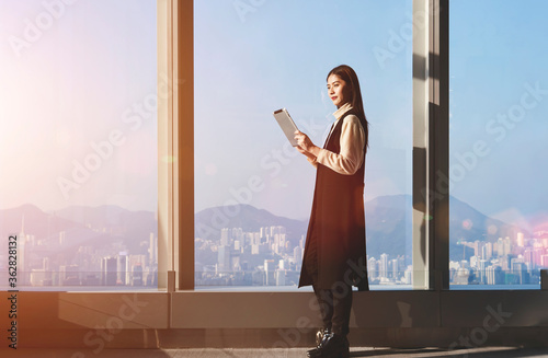 Young Asian businesswoman is using digital tablet for searching needed information for upcoming conference, while is standing in office interior against big window with city view on background
