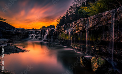 Fotografie, Obraz Scenic View Of Waterfall Against Sky During Sunset