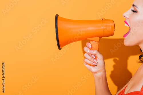 Photo side view of young woman screaming in megaphone on orange