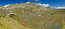 Castelluccio Di Norcia, Italy - July 2020: Wide View With The Town On The Left Still Rebuilding After The 2016 Earthquake And The Colorfull Lentil Fields On The Left