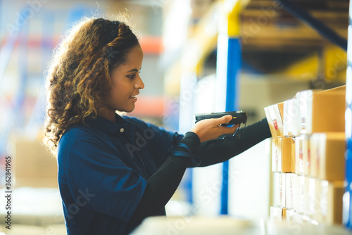 Photo warehouse worker using bar code scanner to analyze newly arrived goods for further placement in storage department, Working at warehouse