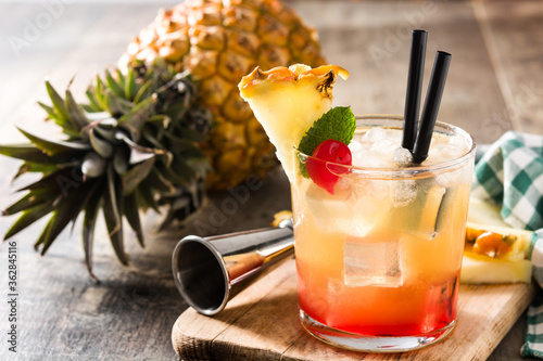 Fototapeta Cold mai tai cocktail with pineapple and cherry on wooden table. 	 obraz