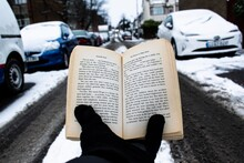 Cropped Hands Reading Book On Road In City During Winter