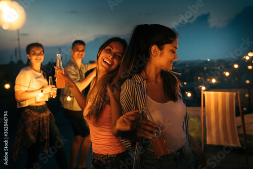 Having a great time with friends, having fun at rooftop party Fotobehang