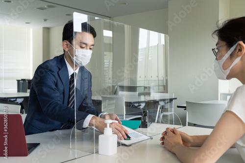 アクリルパーティション越しに話すビジネスマン 感染対策 ソーシャルディスタンス Fototapet
