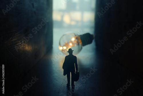 Fotografía Surreal image of person in dark corridor looking at glowing light bulb