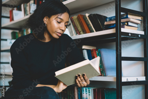 Obraz na plátně Serious female dark skinned student concentrate on reading book in college libra