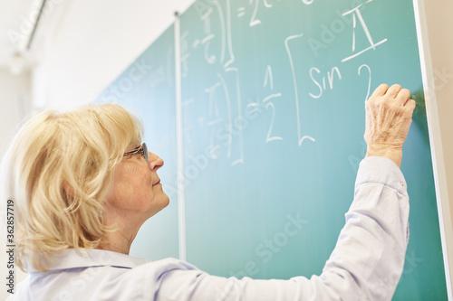 Low Angle View Of Teacher Writing On Blackboard In Classroom Wallpaper Mural