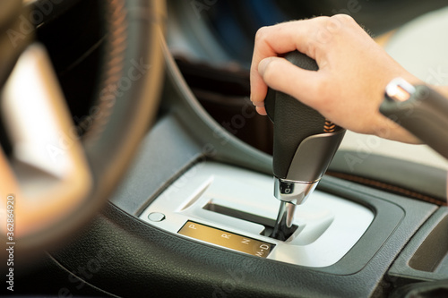 Close up of woman driver holding her hand on automatic gear shift stick driving as car Fototapeta