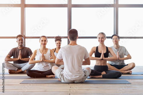 Multiethnic group of young people attending yoga class in modern studio Wallpaper Mural