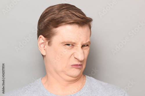 Portrait of funny man grimacing from disgust and squeamishness Fototapet