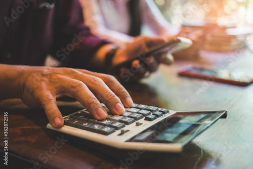 Fototapeta businessman hand using calculator Calculating bonus(Or other compensation) to employees to increase productivity.Writing paper on desk.Selective Focus obraz