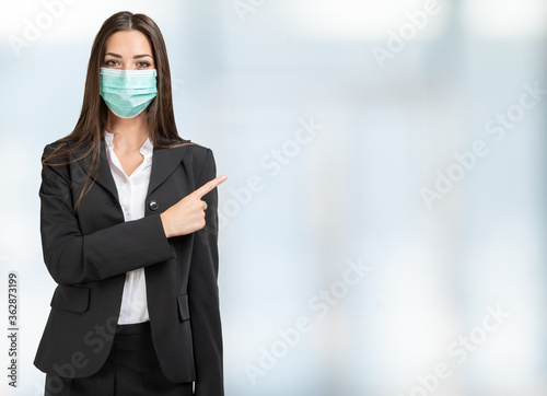 Masked businesswoman pointing her finger to a bright space