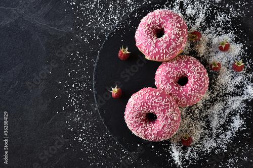 Photo Pink farbene Donuts auf einer schwarzen Schieferplatte und einen dunklen Tisch -