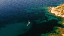 Aerial Shot Of A Dark Blue Ocean With A Boat And A Piece Of Land Seen On A Side