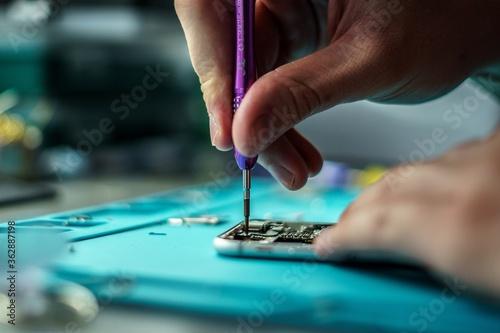 Fototapeta Closeup shot of a person repair a mobile in mobile repair smartphone workshop obraz