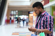App With Discounts. Smiling Black Man Using Smartphone In Shopping Mall