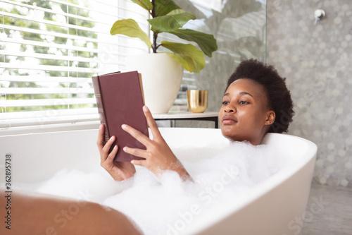 Woman reading book in a bathtub