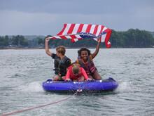 Kids Tubing Behind Motorboat F...