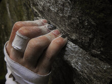 Rock Climbers Fingers Holding On To A Crimp On Rock, While Bouldering, With Chalk And Tape On Hand. Hanging On To The Edge Of A Rock, Close-up.