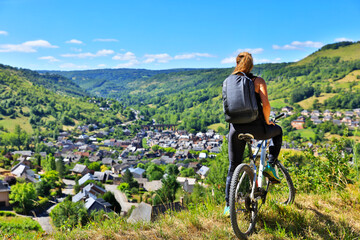 active woman biking countryside- Aveyron in France