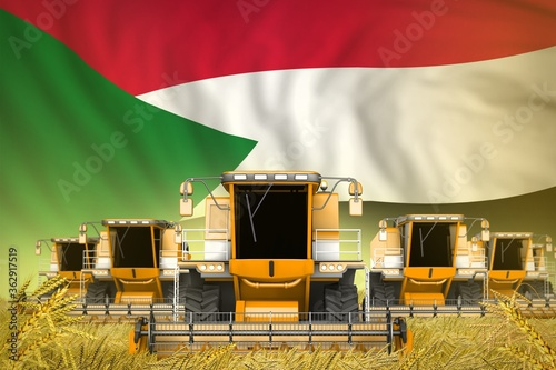 Valokuva a lot of yellow farming combine harvesters on rural field with Sudan flag backgr