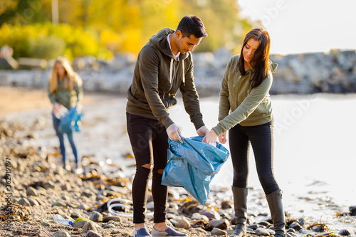Photo Team of environmental conservation volunteers cleaning beach on sunny day