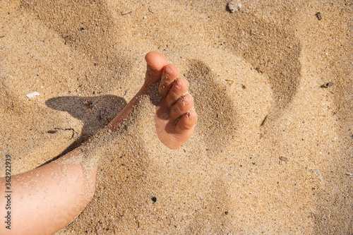 Foot in sand.  child human bare feet buried in seaside photograp