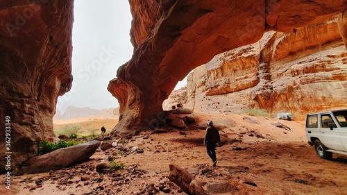 Fotografiet Rear View Of Man Walking B Y Car On Rock Formation