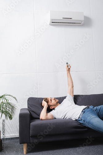 Fotomural confused man holding remote controller and suffering from heat with broken air c
