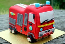 Closeup Shot Of A Red Fire Truck Cake On A Wooden Table