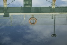 Reflection Of A Pier With Lifebuoy Hanging On A Metal Bar
