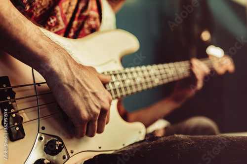 Fototapeta Close up of male hand playing electric guitar in the dark