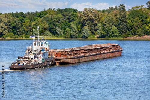 Canvas Print A river tugboat with an empty rusty barge goes crosses a wide river