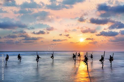 Obraz na plátně Fishermen on stilts in silhouette at the sunset in Galle, Sri Lanka