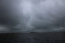 Stormy Weather At A Dutch Lake With Dark Sky And Grey Clouds.