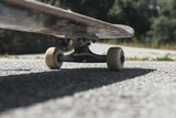 Closeup of a skateboard on the ground under the sunlight with a blurry background